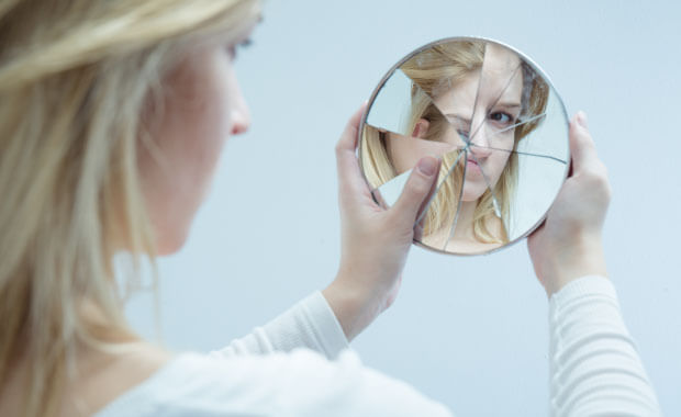 documenting low self-esteemwith young women looking into a broken mirror